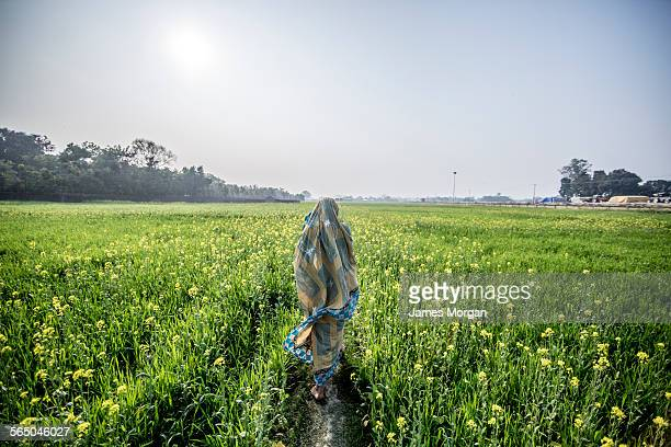 Woman walking through mustard field