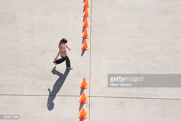 Woman walking through opening in row of traffic cones