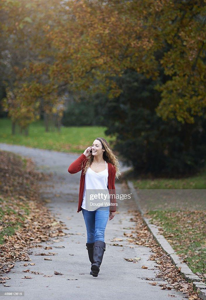 Woman walking through park using mobile phone. : Stock Photo
