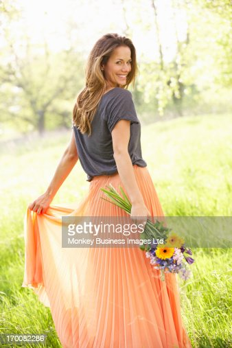 Woman Walking Through Summer Field Carrying Bouquet Of Flowers : Stock Photo
