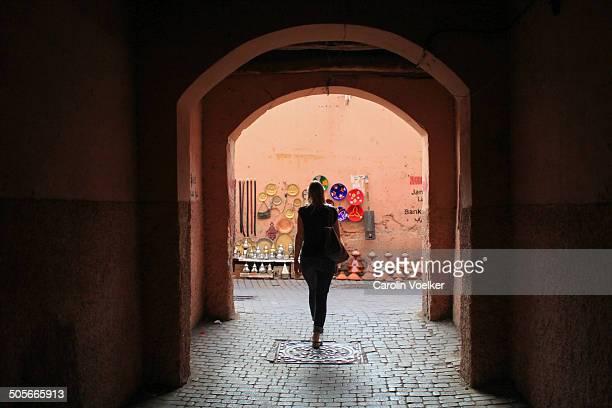 Woman walking through tunnel, Marrakech