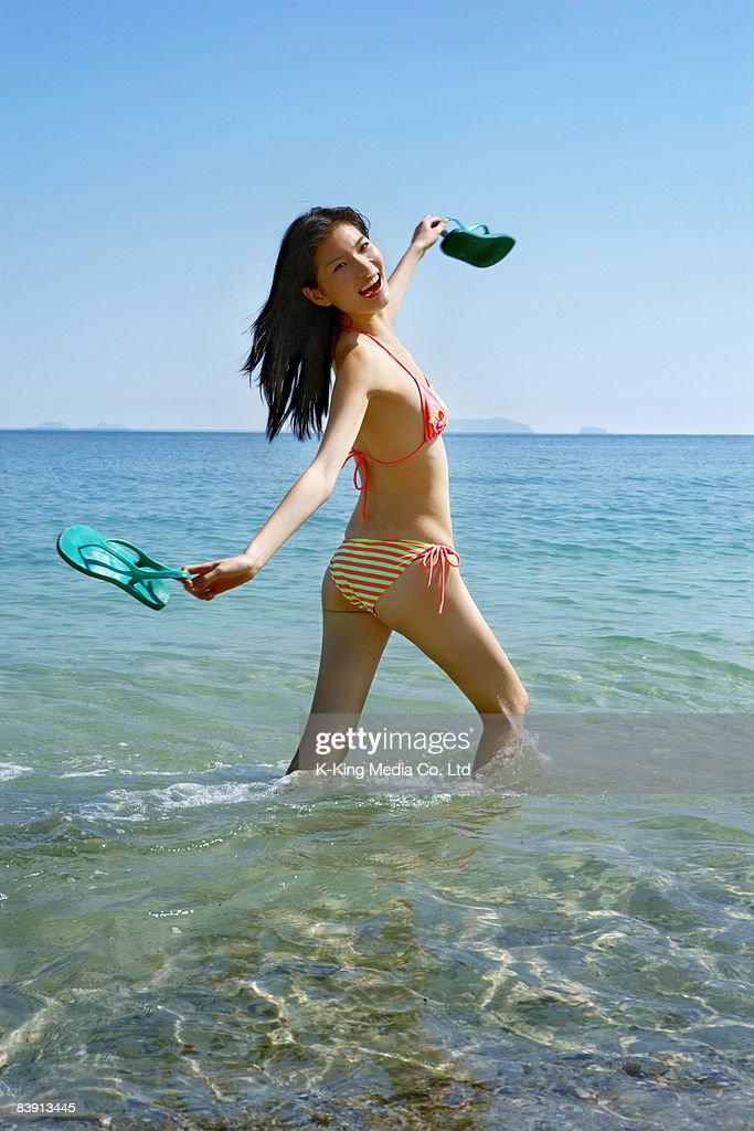 Woman walking through water, holding shoes. : Stock Photo