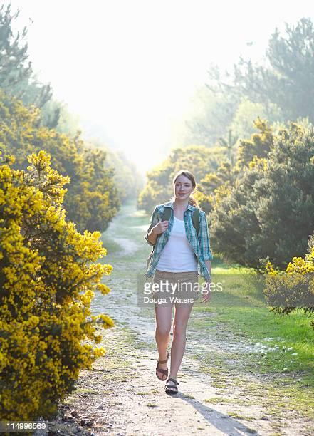 Woman walking through woodland.