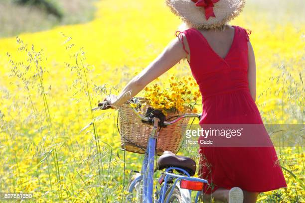 Woman walking through yellow flower meadow with bycicle