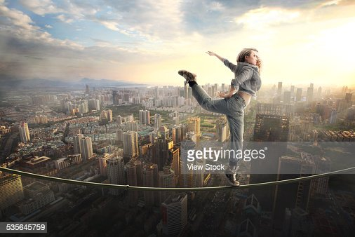 Woman walking tightrope over city