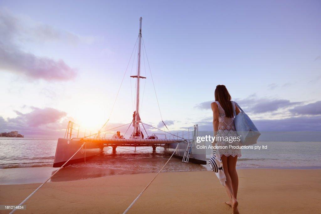 Woman walking to boat on beach : Stock Photo