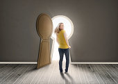 Woman walking towards keyhole shaped doorway with light ikn dark grey room