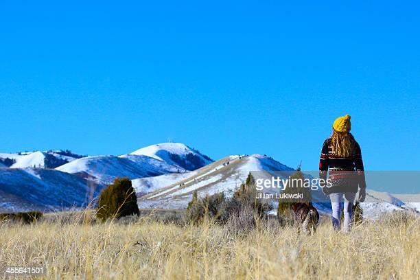 Woman Walking Towards Snow Covered Peaks