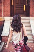 Woman walking towards stairs to front door