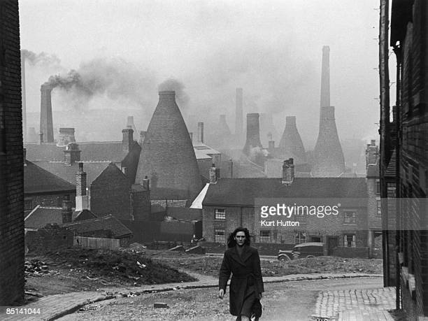 A woman walking up a street in StokeonTrent Staffordshire with smoking bottle kilns belonging to potteries visible in the background 2nd March 1946...