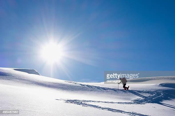 Woman walking up snowy hillside
