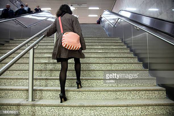 Woman walking up stairs with escalators on either side
