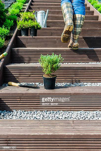 Woman walking up the garden stairs, resting after gardening works