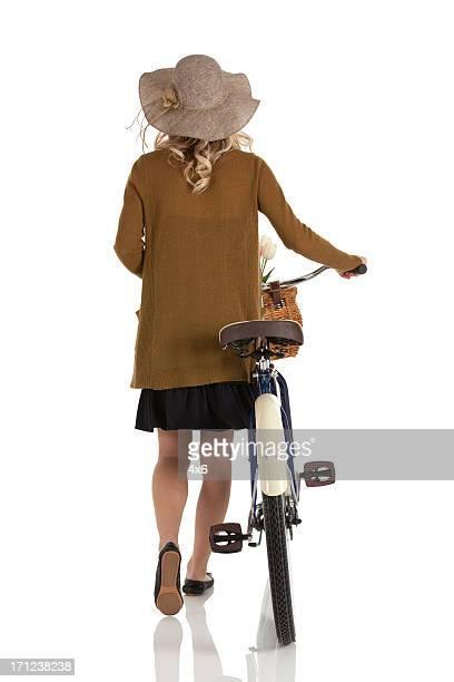 Femme marchant avec vélo