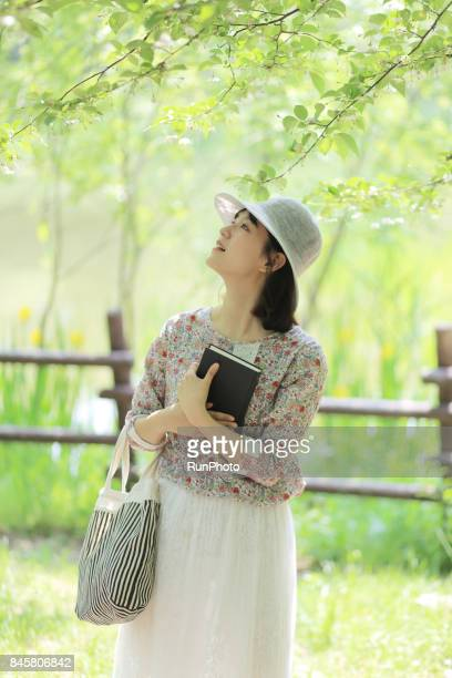 woman walking with a book in the park