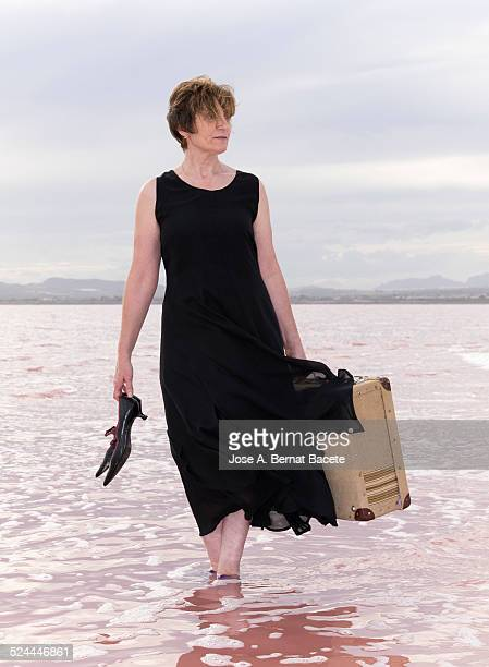 Woman walking with a suitcase within of the water