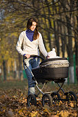 Woman walking with baby in pram in park