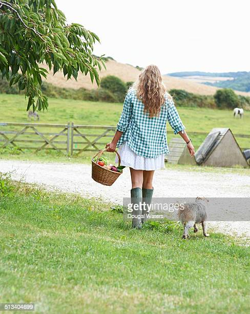Woman walking with basket of vegetables on farm.