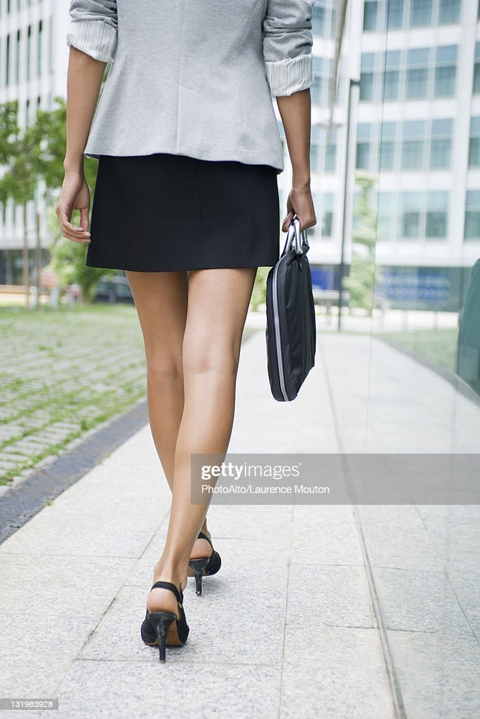 Woman walking with briefcase, low section