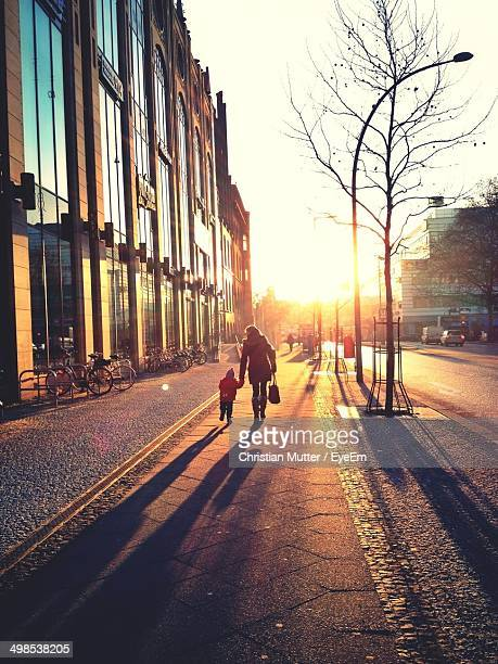 Woman walking with child on sidewalk during sunrise
