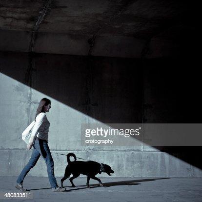Woman walking with dog under bridge : Stock Photo