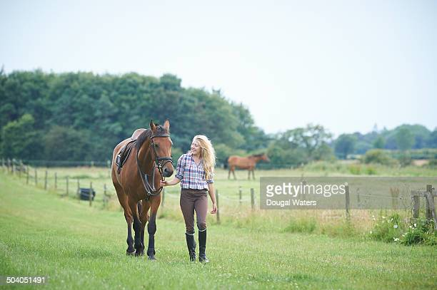 Woman walking with horse in paddocks.