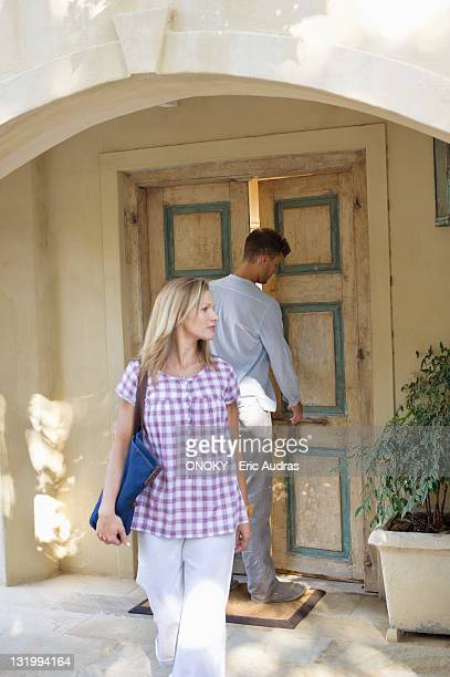 Woman walking with man locking the door in the background