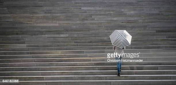 Woman walking with open umbrella