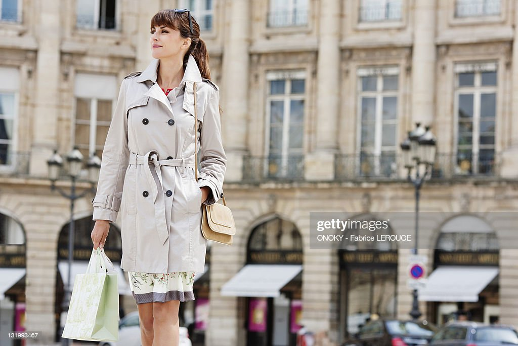 Woman walking with shopping bags on a street, Paris, Ile-de-France, France