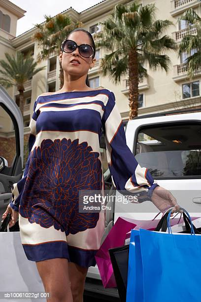 Woman walking with shopping bags out of car, low angle view