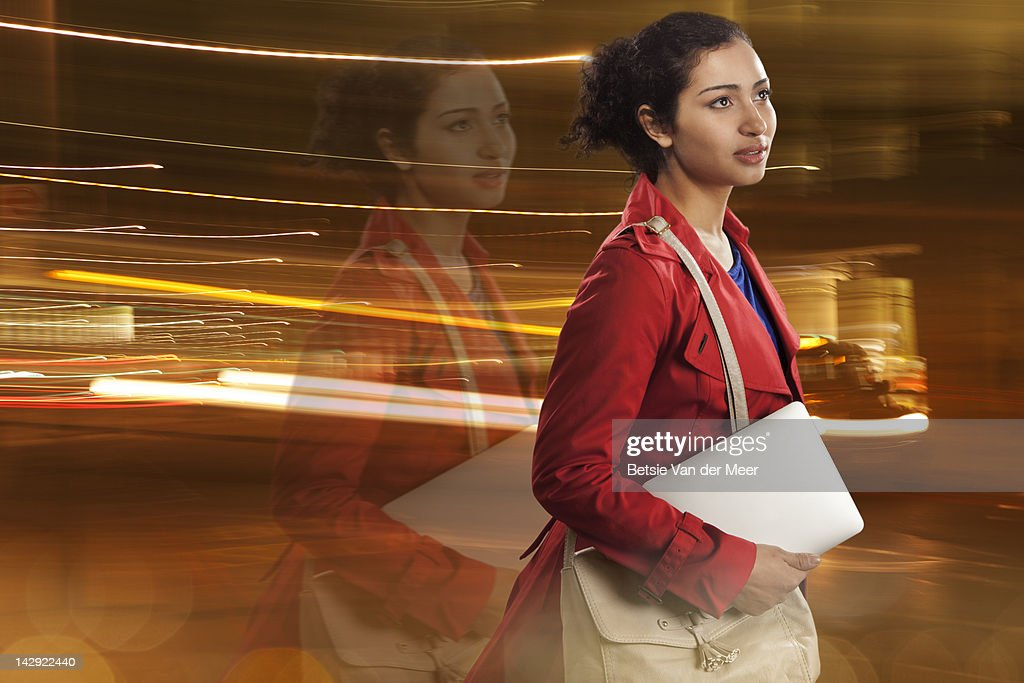 Woman walking with ipad in city at night.