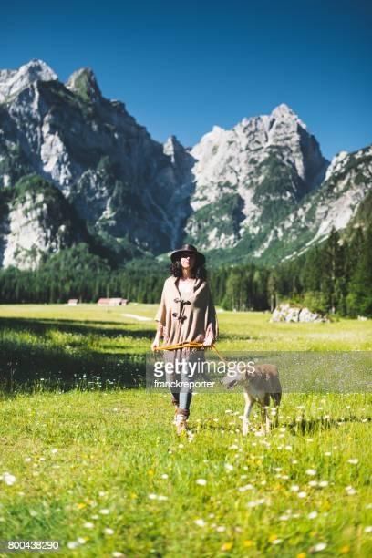 Frau zu Fuß mit dem Hund in den Bergen