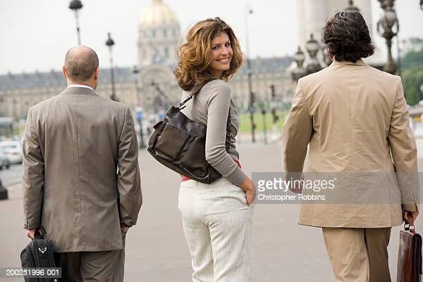 Woman walking with two male colleagues, turning head, smiling