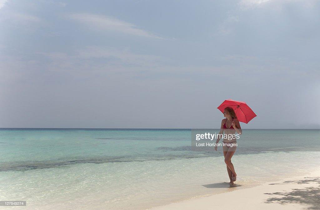Woman walking with umbrella on beach