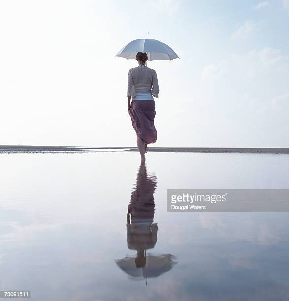 Woman walking with umbrella on beach, rear view, low angle view
