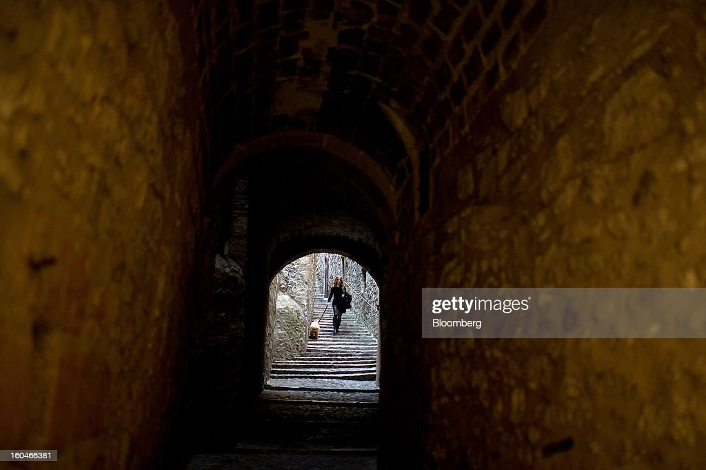 A woman walks a dog down stairs between buildings in downtown Girona, Spain, on Thursday, Jan. 31, 2013. Spain's recession deepened more than economists forecast in the fourth quarter as the government's struggle to rein in the euro region's second-largest budget deficit weighed on domestic demand. Photographer: David Ramos/Bloomberg via Getty Images