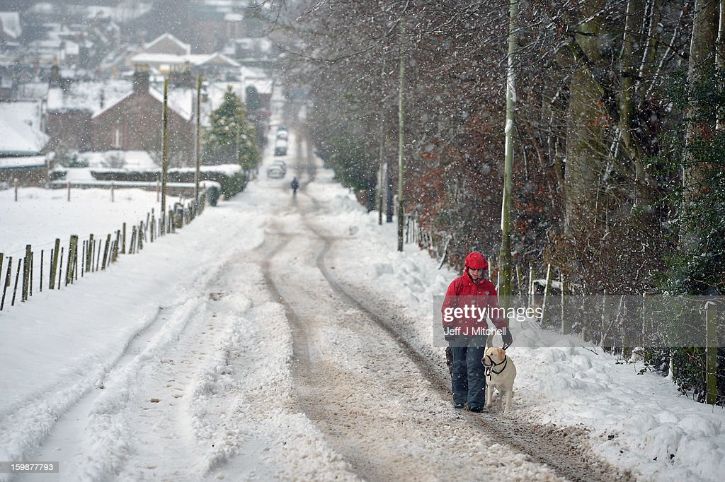 A woman walks a dog in Blairgowrie on January 22, 2013 in Blairgowrie, United Kingdom.The Met Office has issued a red weather warning for parts of the Uk and advising against all non-essential travel as up to 30cm of snow is expected to fall in some areas today. The adverse weather has closed nearly 5,000 schools and caused many airports to cancel flights.