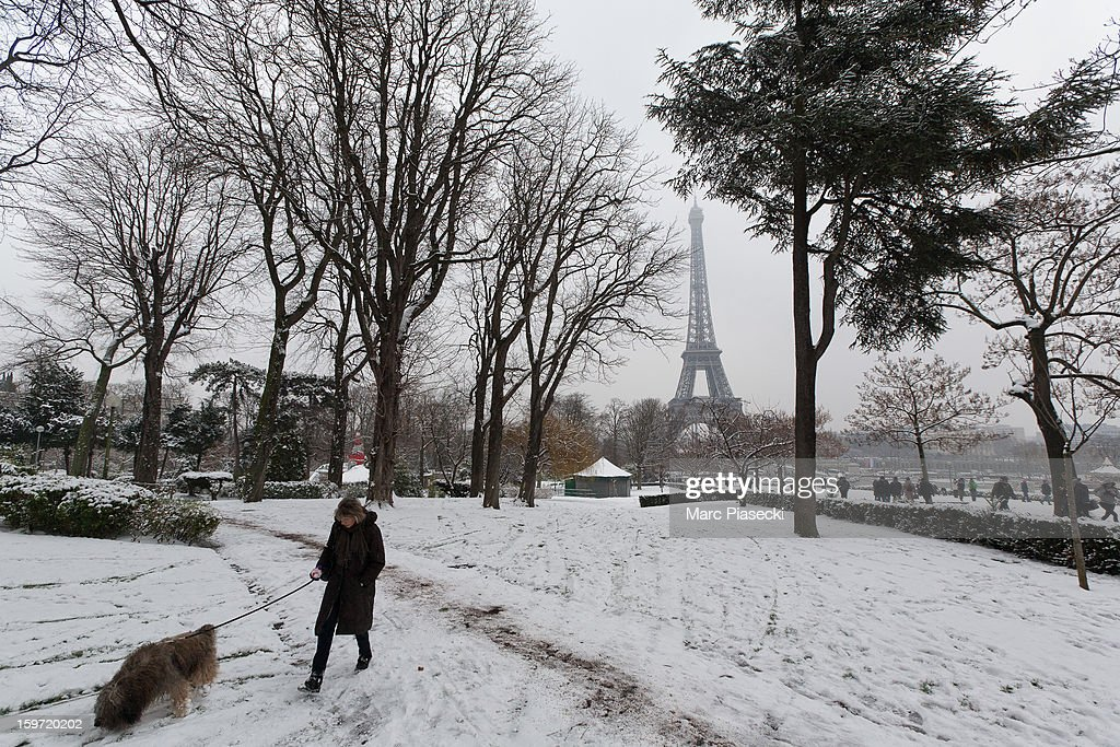 A woman walks a dog in the snow near the Eiffel Tower on January 19, 2013 in Paris, France. Heavy snowfall fell throughout Europe and the UK causing travel havoc and white layers of pretty scenery.
