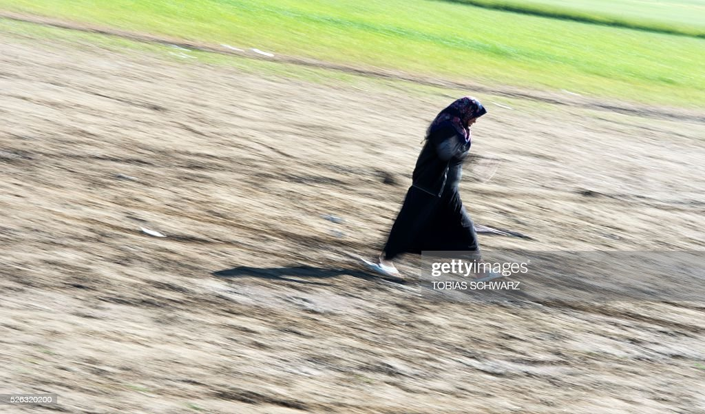 A woman walks across a field at a makeshift camp for migrants and refugees near the village of Idomeni, not far from the Greek-Macedonian border, on April 30, 2016. Some 54,000 people, many of them fleeing the war in Syria, have been stranded on Greek territory since the closure of the migrant route through the Balkans in February. / AFP / TOBIAS
