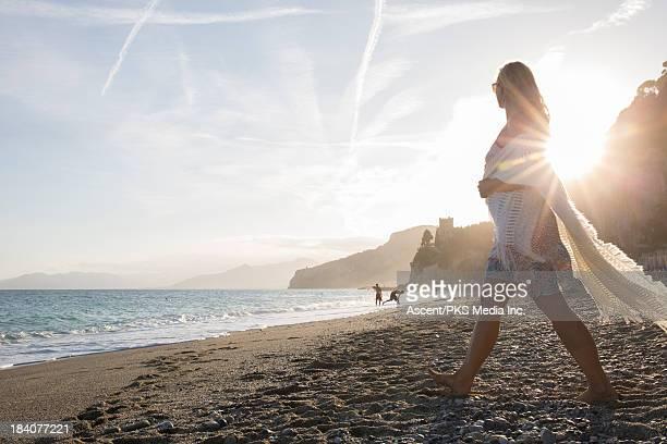 Woman walks across beach at sunrise, with shawl