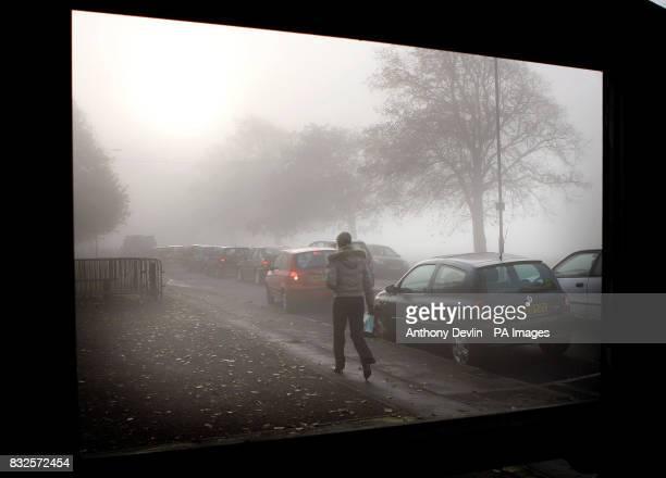 A woman walks across the Clifton Downs towards Bristol city centre as a heavy autumn mist descends over the city