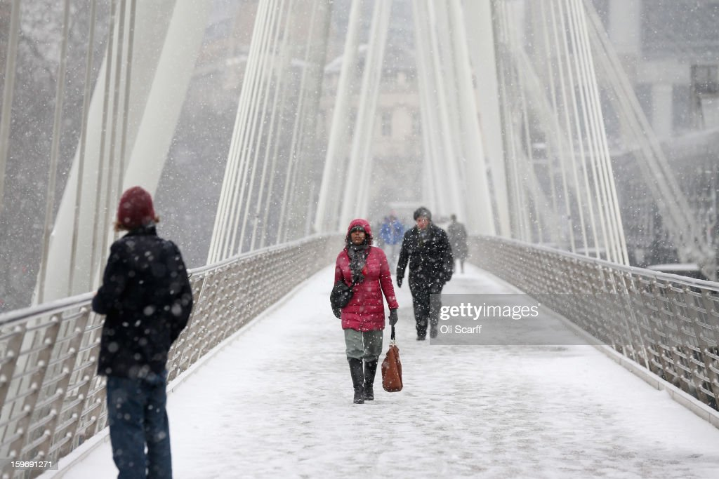 A woman walks across the snow-covered Golden Jubilee Footbridge towards the South Bank of the river Thames as snow falls on January 18, 2013 in London, England. Widespread snowfall is affecting most of the UK with school closures and transport disruption. The Met Office has issued a red weather warning for parts of Wales, advising against all non-essential travel as up to 30cm of snow is expected to fall in some areas today.