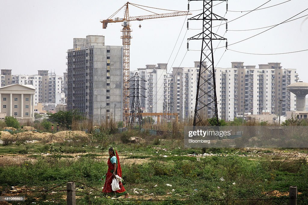 A woman walks across wasteland as newly constructed and under construction residential buildings stand close to pylons in the background in Gurgaon, India, on Wednesday, March 26, 2014. Indian stocks rose, sending the benchmark index to a record, after the rupee rose to an eight-month high and sovereign bonds gained on speculation the worlds largest democracy will elect a government capable of reviving economic growth. Photographer: Kuni Takahashi/Bloomberg via Getty Images