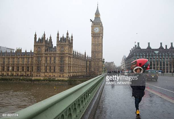 A woman walks across Westminster Bridge past the Houses of Parliament during a snow flurry in London on January 13 2017 The Met Office issued severe...