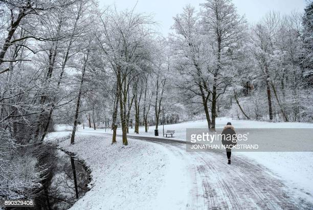A woman walks after snow fall on December 11 2017 in Sundbyberg near Stockholm High winds and heavy snow in Europe on Monday stranded thousands of...