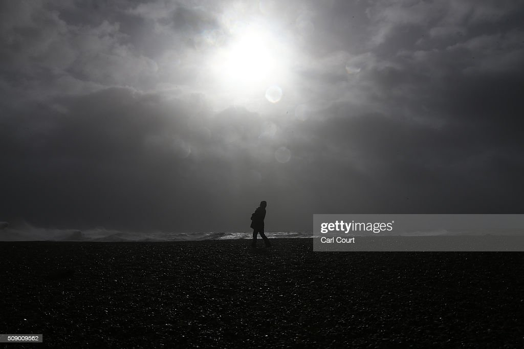 A woman walks along a beach on February 8, 2016 in Newhaven, East Sussex. Storm Imogen is the ninth named storm to hit the UK this season. This year's storms are being named in an effort by the Met Office and Met Eireann to increase public awareness and safety. They were named by public ballot and there are no names for the letters Q, U, X, Y and Z.