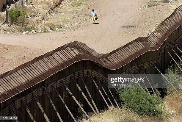 A woman walks along a dirt road on the Mexican side of the border next to the steel wall that separates Nogales Sonora Mexico May 14 2006 from...