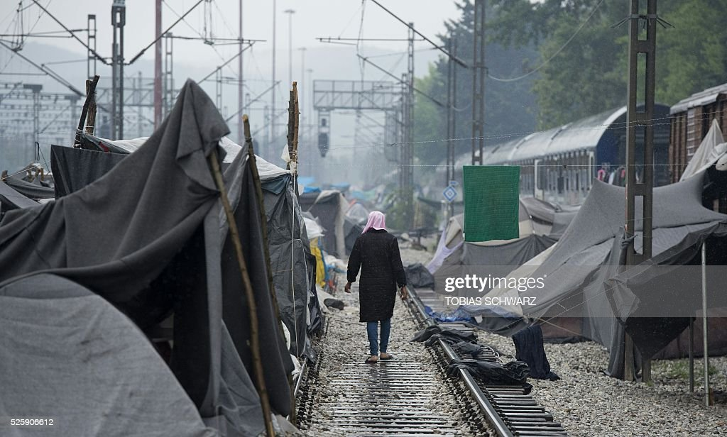 A woman walks along a rail track past tents at a makeshift camp for migrants and refugees near the village of Idomeni not far from the Greek-Macedonian border on April 29, 2016. Some 54,000 people, many of them fleeing the war in Syria, have been stranded on Greek territory since the closure of the migrant route through the Balkans in February. / AFP / TOBIAS