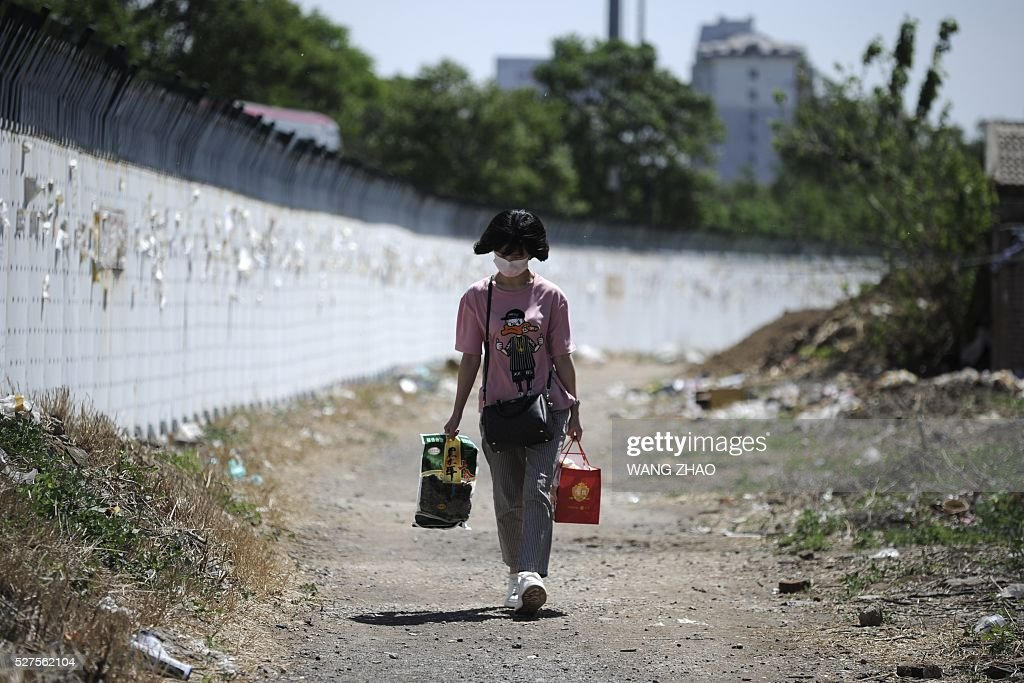 A woman walks along a road outside a subway station in Beijing on May 3, 2016. China's economic recovery stabilished in April, an official factory activity gauge showed on May 1, as the property market recovered and credit grew. / AFP / WANG
