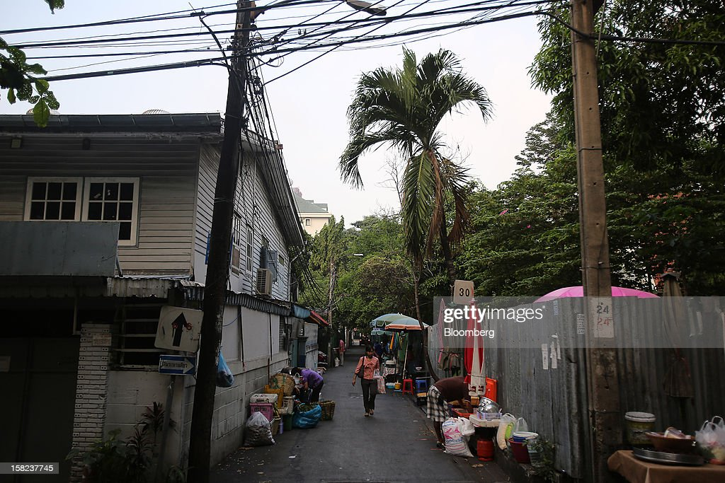 A woman walks along a side street off Langsuan road in Bangkok, Thailand, on Tuesday, Dec. 11, 2012. The Crown Property Bureau owns about 41,300 rai (66 square kilometers) of land across the country, about a fifth of which is in Bangkok, according to Aviruth Wongbuddhapitak, an adviser to the CPB who sits on the board of two of its subsidiaries. Photographer: Dario Pignatelli/Bloomberg via Getty Images